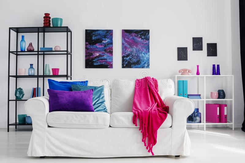 Vertical view of stylish living room with comfortable white couch with pink blanket and blue and purple pillows, cosmos graphics o. Vertical view of stylish royalty free stock photos