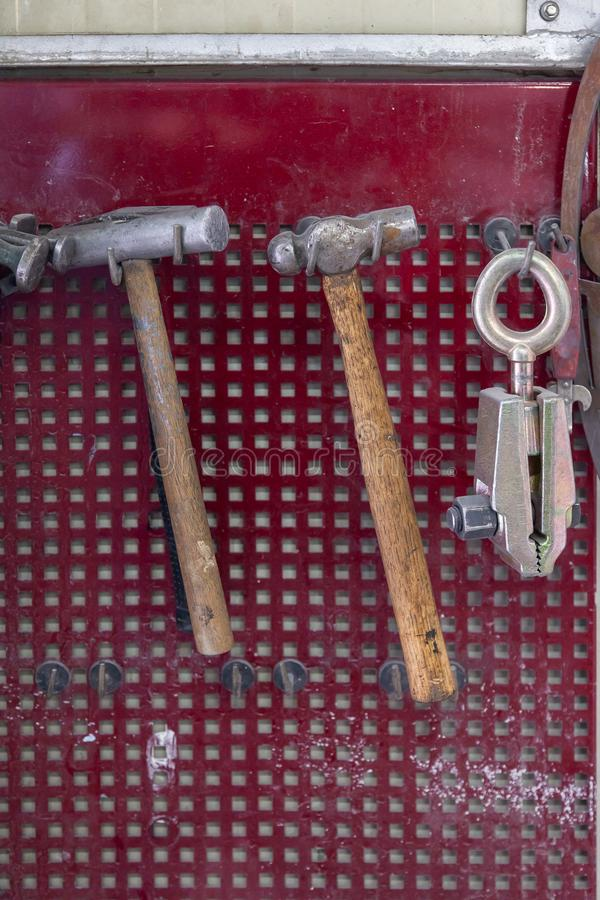 Vertical view of two old hammers with a brown wooden handle and a clamp hanging on the wall in a workshop for carpentry work on a. Red background royalty free stock images