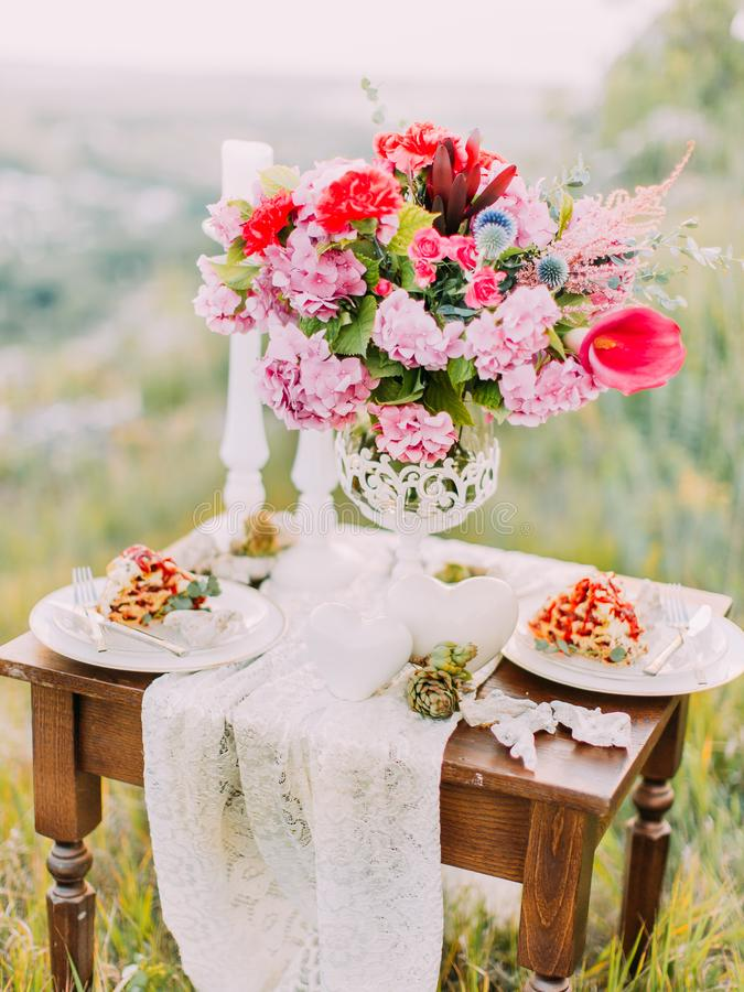 The vertical view of the wedding table set consisted of the bouquet of flowers, cake and candles in the mountains. royalty free stock images