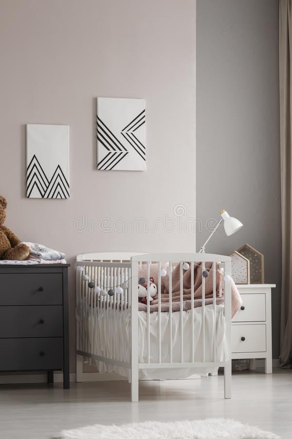 Vertical view of white crib with pastel pink bedding and cotton balls in grey and beige fashionable baby bedroom. Vertical view of white crib with pastel pink stock photo