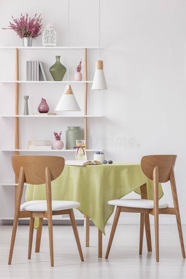 Wooden chairs at round table with olive green tablecloth in bright elegant living room, real photo. Vertical view of wooden chairs at round table with olive royalty free stock photo