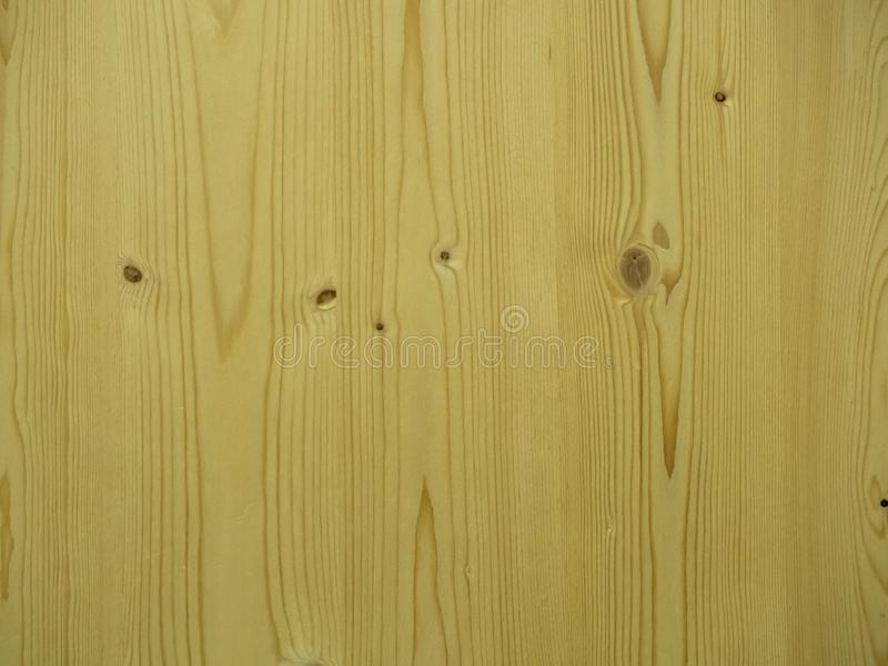 Vertical wall of pine boards in the background. Vertical wall of pine boards with knots as background stock image