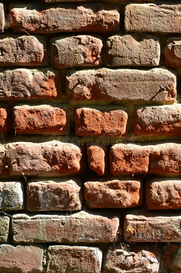 Vertical wall texture of several rows of very old brickwork made of red brick. Shattered and damaged brick wall with pinched corn. Ers stock images