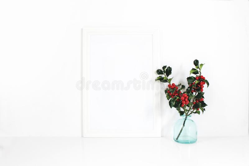 Vertical white blank wooden frame mockup. Holly berry branches in blue glass vase on white table. Styled stock feminine stock images