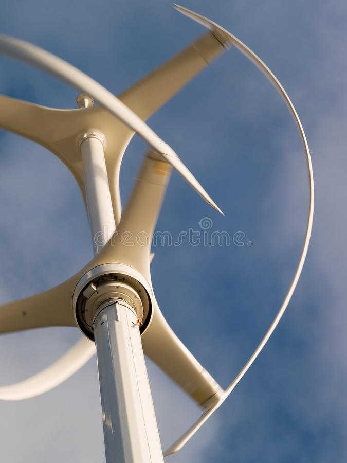 Vertical wind turbine in operation. Vertical axis wind turbine revolving in a brisk wind with motion blur royalty free stock images