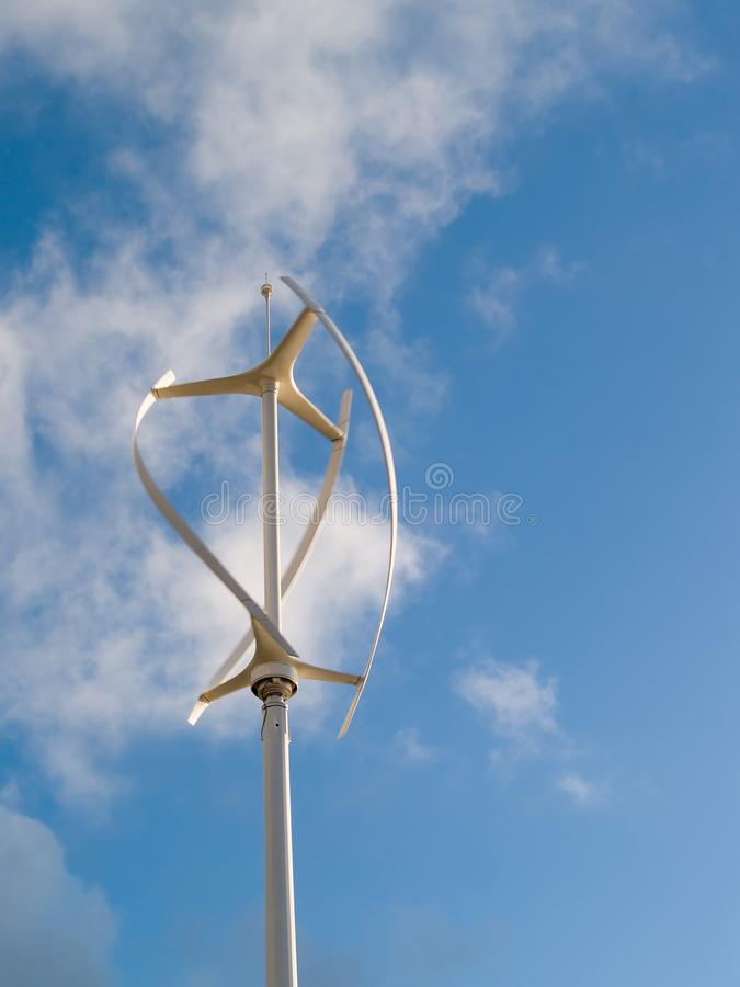 Vertical wind turbine in operation. Vertical axis wind turbine revolving in a brisk wind with motion blur royalty free stock image