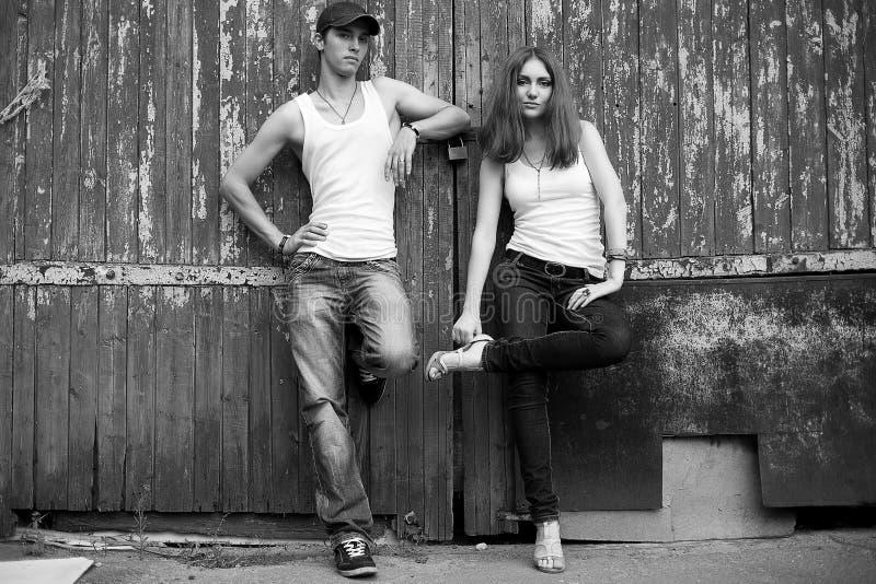 Verticale émotive d'un couple élégant dans des jeans restant ensemble photos libres de droits