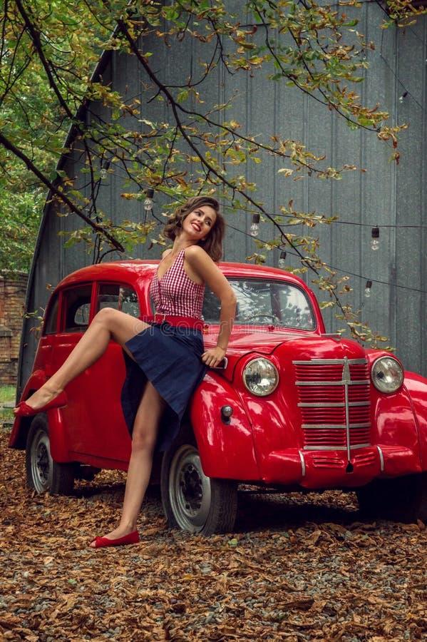 Verticale émotive Fille Pin- posant tout près une rétro voiture russe rouge Le modèle rit fort, flirtatiously montrant les jambes photos libres de droits