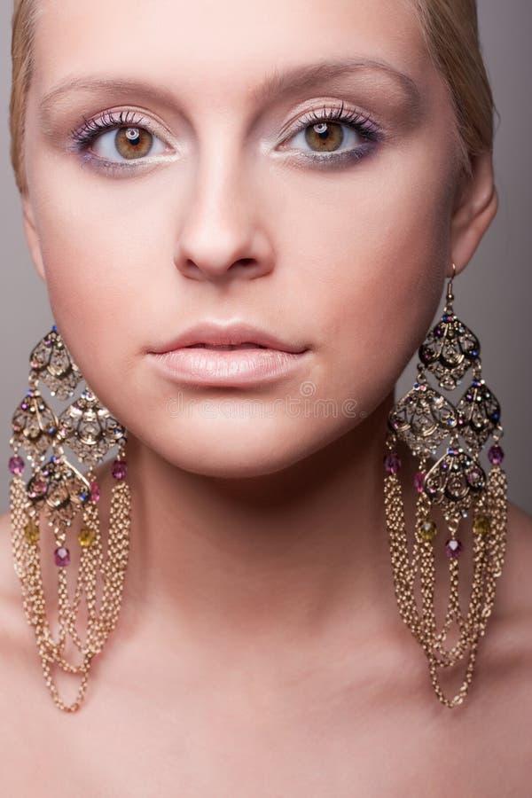 Verticale attrayante de fille avec la boucle d'oreille ethnique photo stock