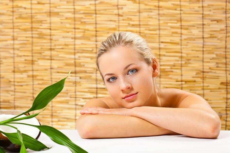 Verticale blonde de fille au-dessus du couvre-tapis en bambou photo stock