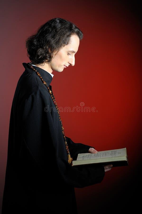 Verticale conceptuelle de prêtre de prière avec la bible images libres de droits