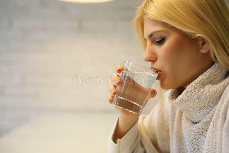 Verticale d'eau potable de jeune femme photographie stock