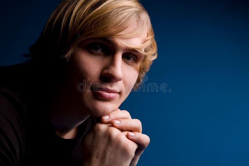 Verticale d'homme blond au-dessus de fond bleu photographie stock