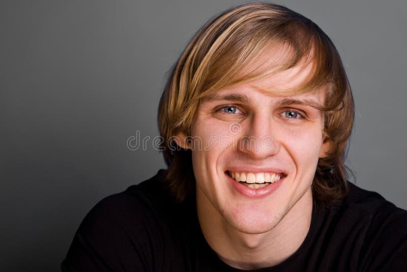 Verticale d'homme blond de sourire au-dessus de fond gris image libre de droits