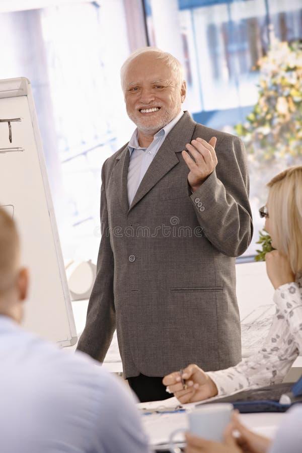 Verticale d'homme d'affaires aîné faisant la présentation photo libre de droits