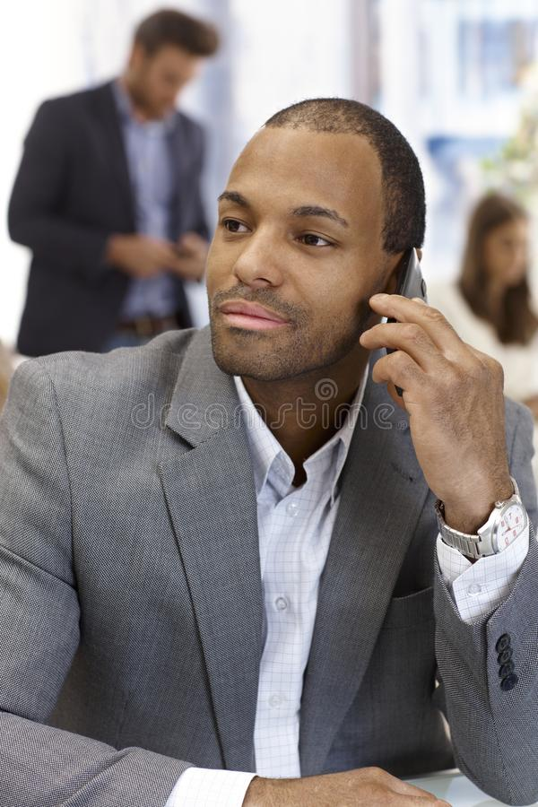 Verticale d'homme d'affaires bel au téléphone image libre de droits