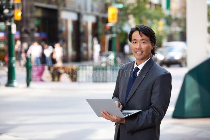 Verticale d'homme d'affaires extérieure avec l'ordinateur portatif photos libres de droits