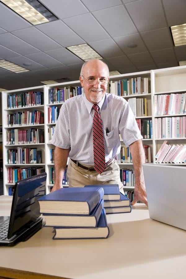 Verticale d'homme mûr à la bibliothèque avec des manuels photographie stock libre de droits