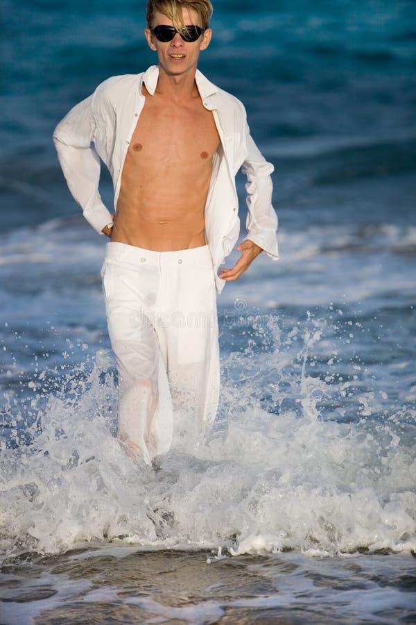verticale d'homme posant des jeunes de rivage de mer image libre de droits