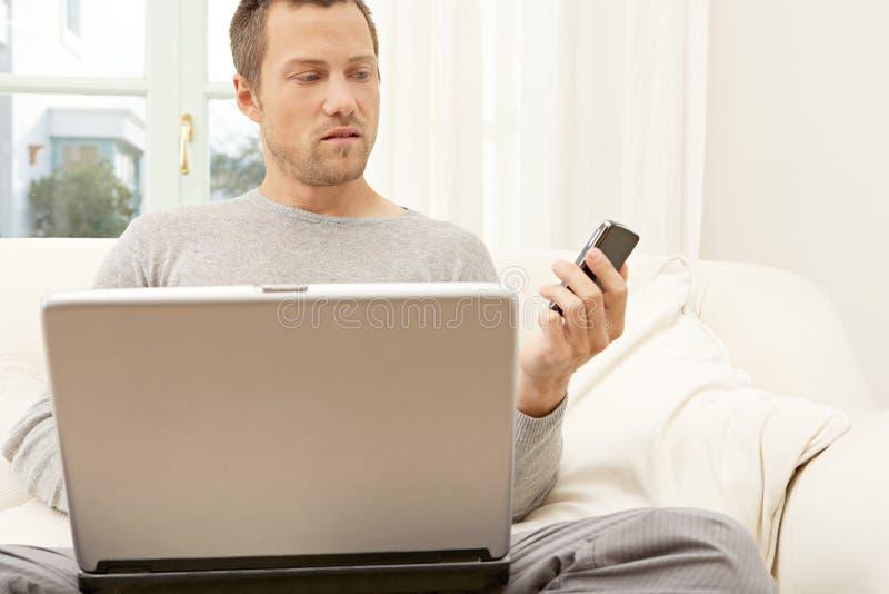 Verticale d'homme professionnel avec l'ordinateur portable et le téléphone intelligent à la maison. photo stock