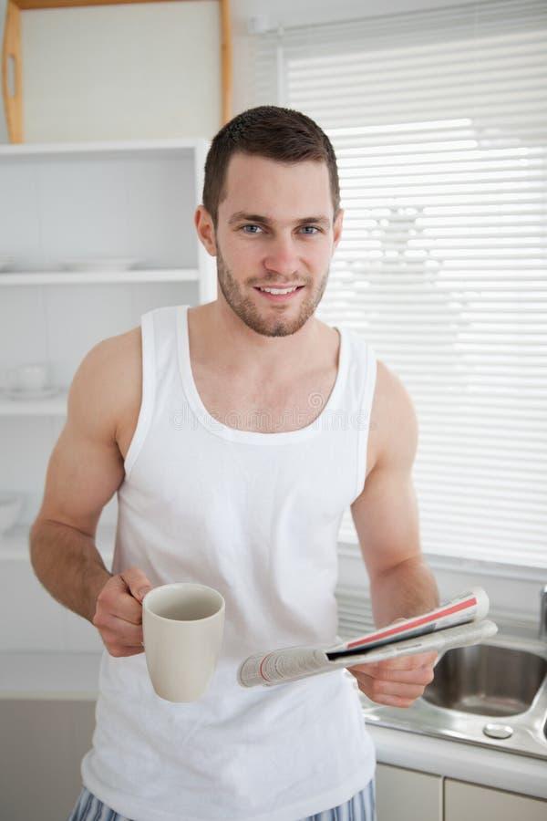 Verticale d'un café potable d'homme tout en affichant les nouvelles photo stock