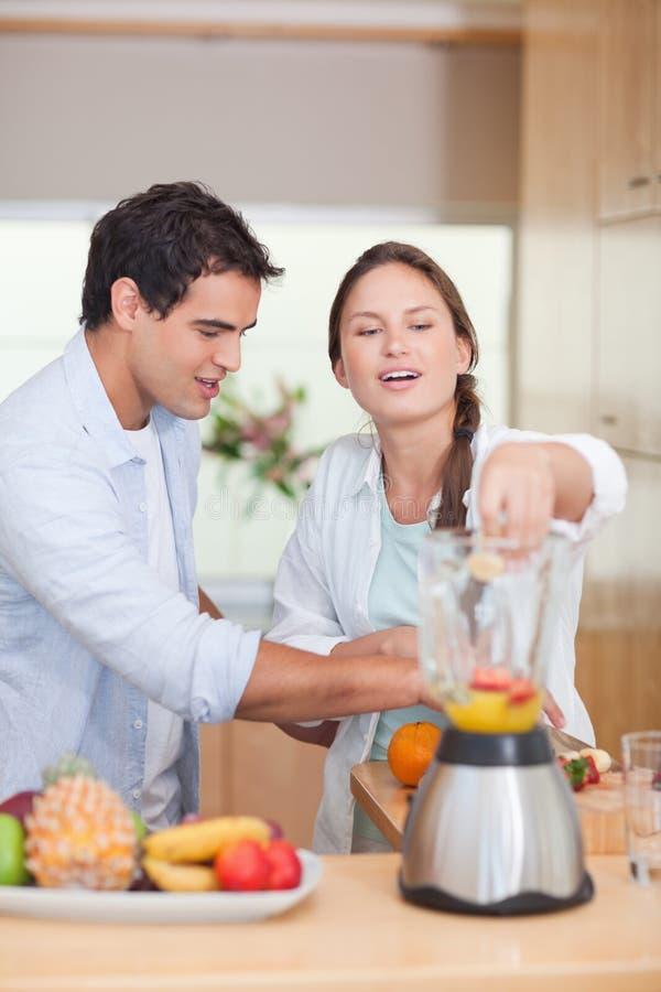 Verticale d'un couple effectuant le jus de fruits frais image stock