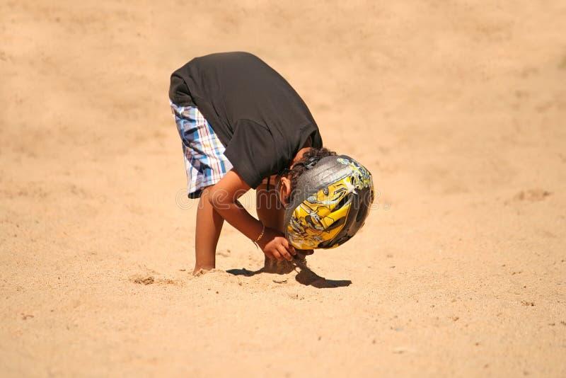 Verticale d'un gosse mignon à l'extérieur, jouant avec le sable image libre de droits