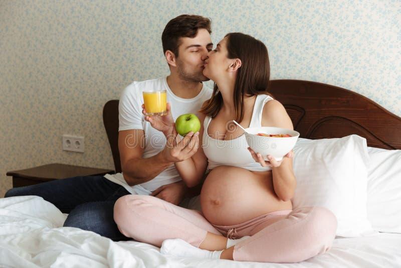 Verticale d'un jeune couple enceinte heureux photos libres de droits