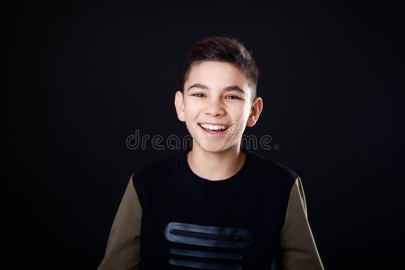 Verticale d'un jeune homme beau souriant, sur le fond noir images stock