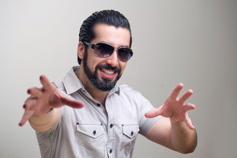 Verticale d'un jeune homme bel faisant des gestes et le sourire de main image stock