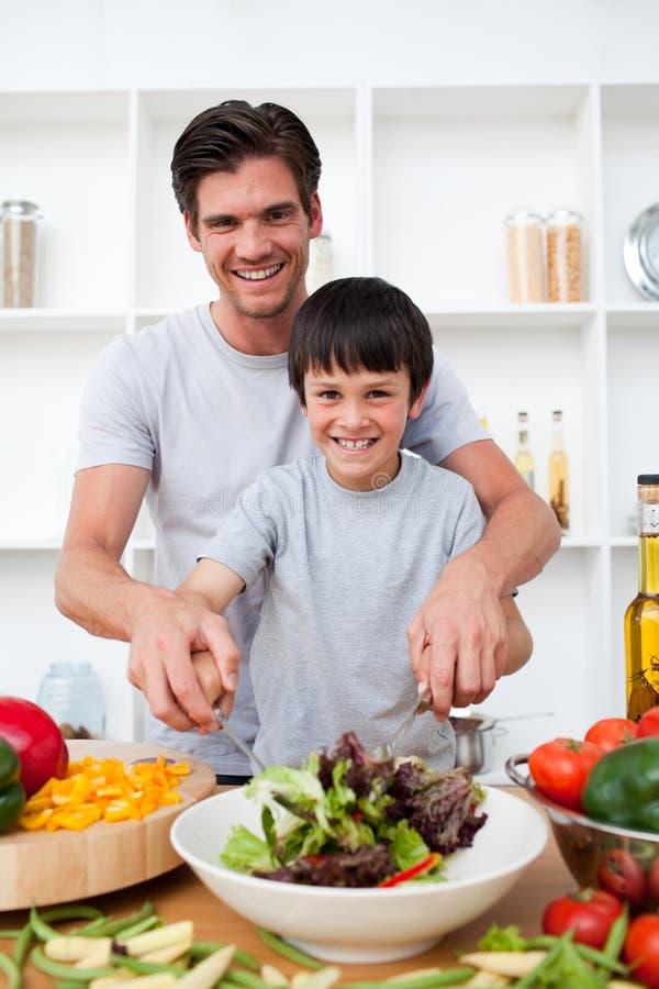 Verticale d'un père heureux faisant cuire avec son fils photographie stock