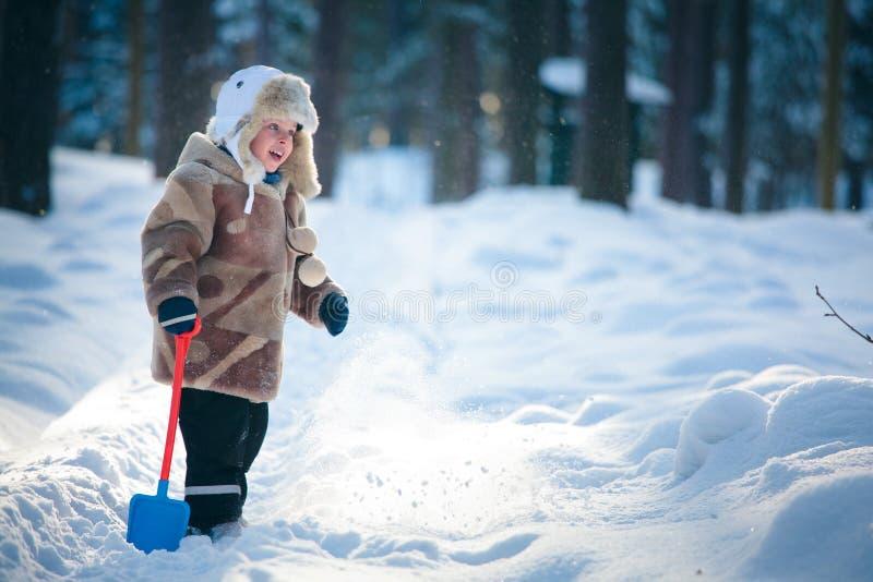 Verticale d'un petit garçon dans une forêt de l'hiver photographie stock