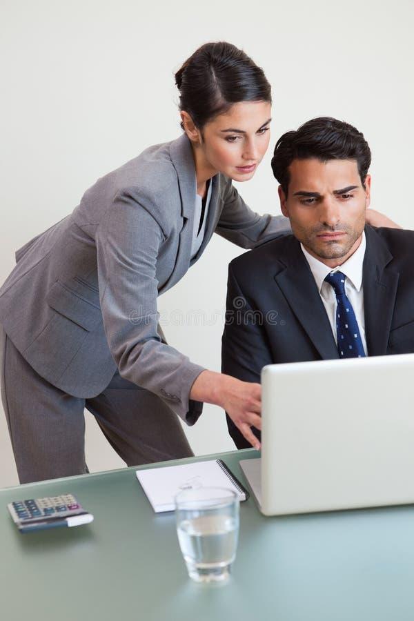 Verticale d'une équipe orientée d'affaires travaillant avec un ordinateur portable image stock