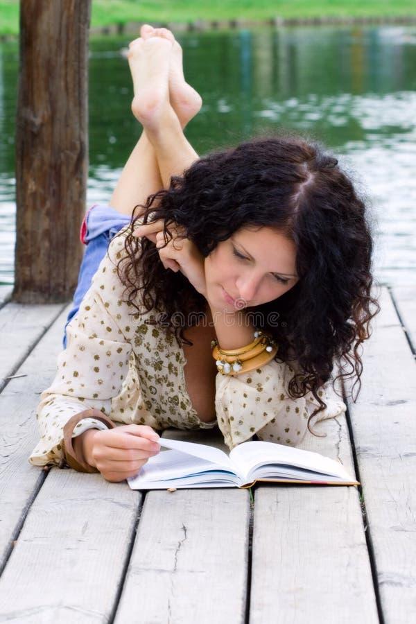Verticale d'une belle femme affichant un livre image stock