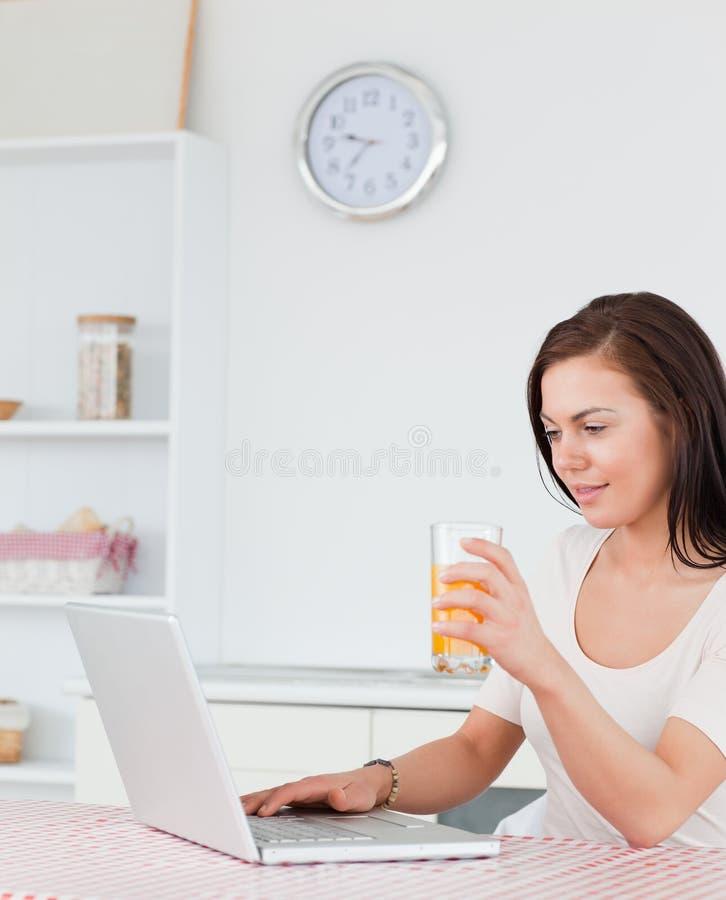 Verticale d'une femme à l'aide de son ordinateur portatif photographie stock libre de droits