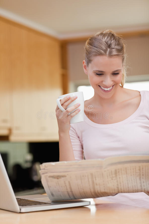 Verticale d'une femme affichant les nouvelles tout en ayant le thé images stock
