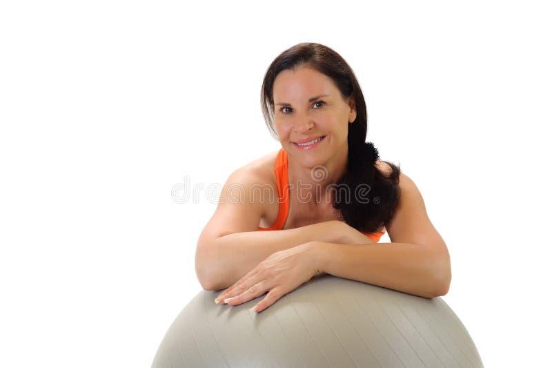 Verticale d'une femme avec une bille d'exercice de Pilates images libres de droits