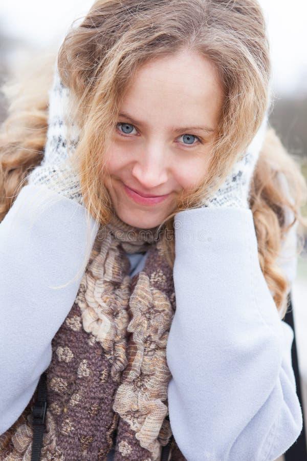 Verticale d'une femme figée de chauffage par des mitaines de laines photos libres de droits