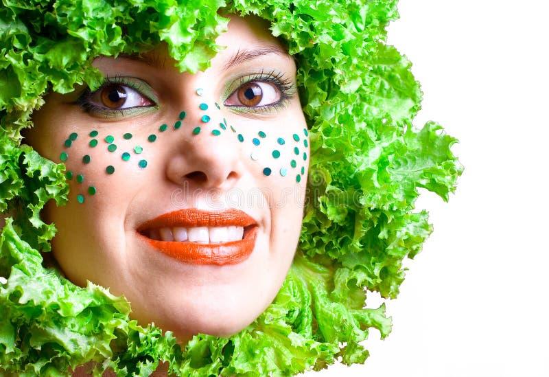 Verticale d'une fille de beauté avec de la salade dans une tête photographie stock