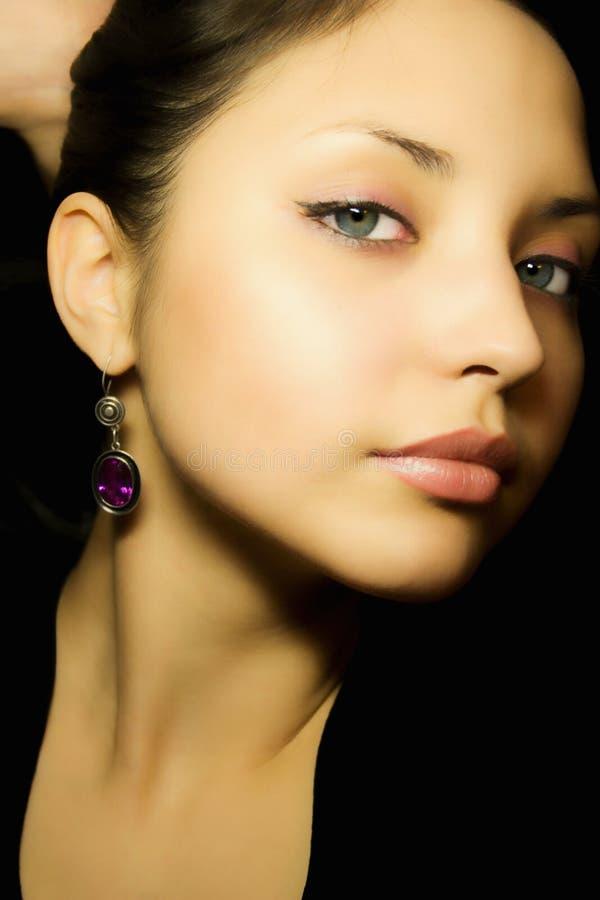 Verticale d'une jeune belle fille avec des boucles d'oreille photo stock