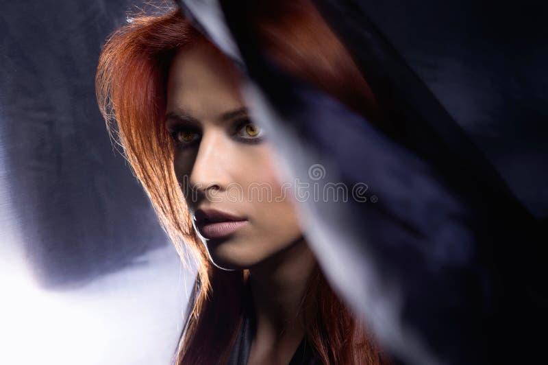 Verticale d'une jeune femme rousse en soie bleue images stock