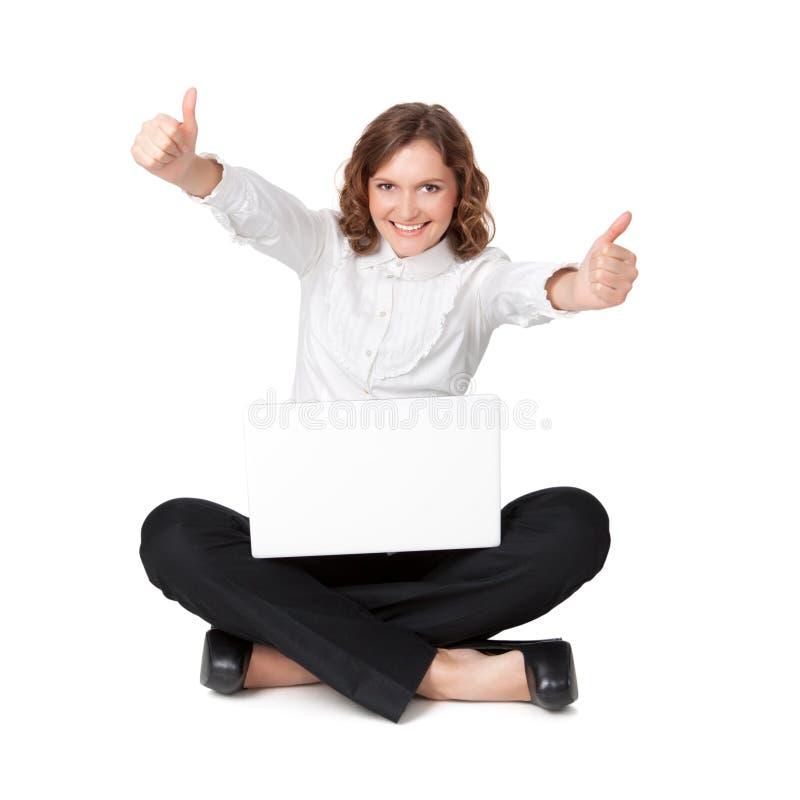 Verticale d'une jolie jeune femme s'asseyant devant son ordinateur portable photo libre de droits
