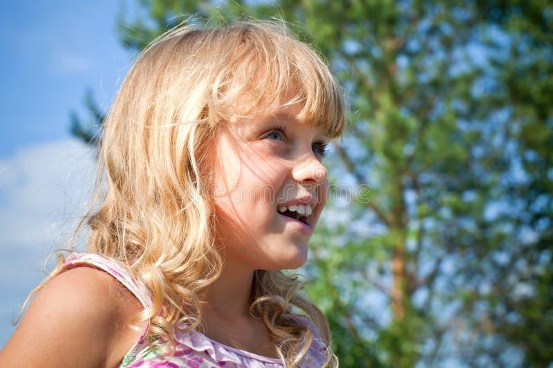 Verticale d'une petite belle fille blonde de sourire photographie stock