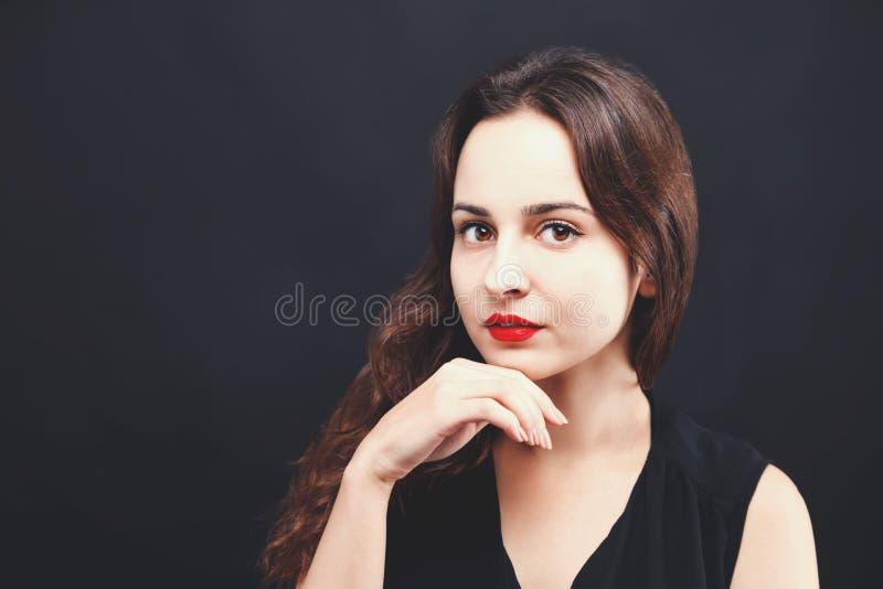 Verticale de belle femme dans la robe noire photographie stock
