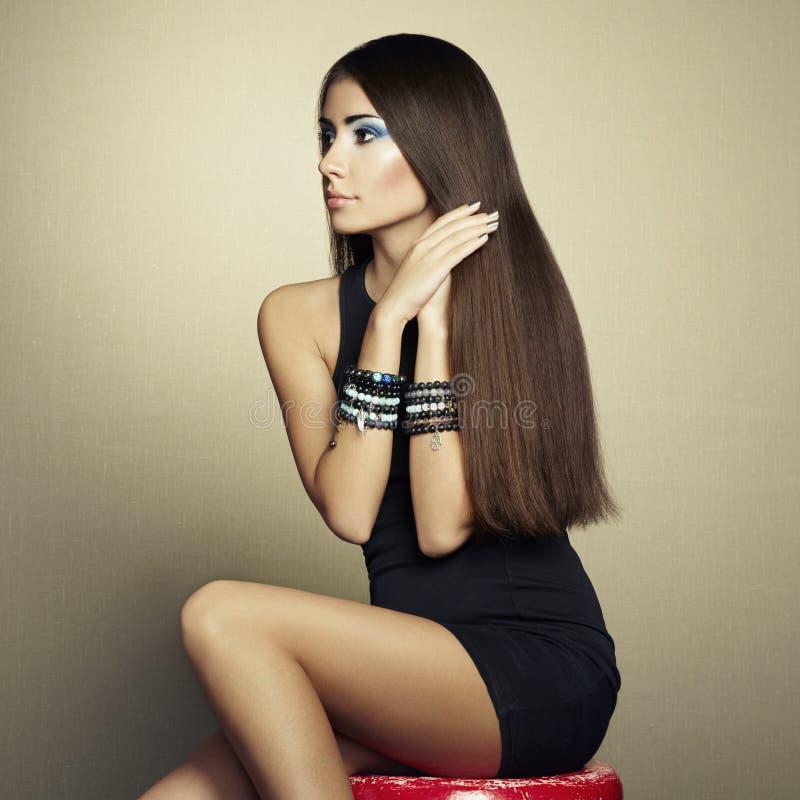 Verticale de belle femme de brune dans la robe noire image stock