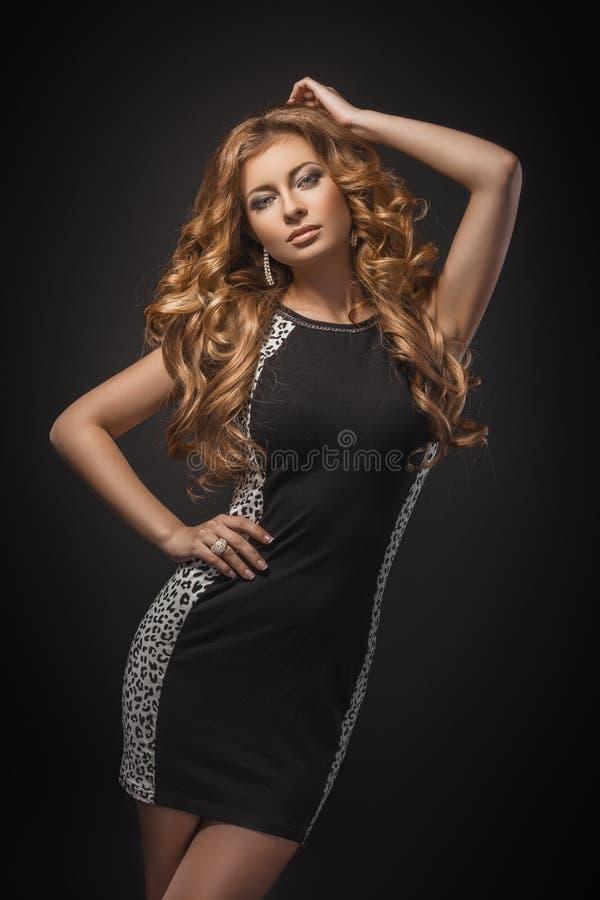 Verticale de belle jeune fille blonde dans la robe noire images libres de droits