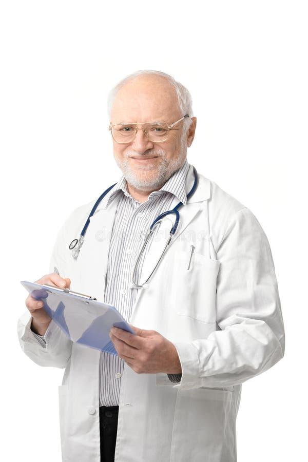 Verticale de docteur aîné regardant l'appareil-photo photographie stock libre de droits