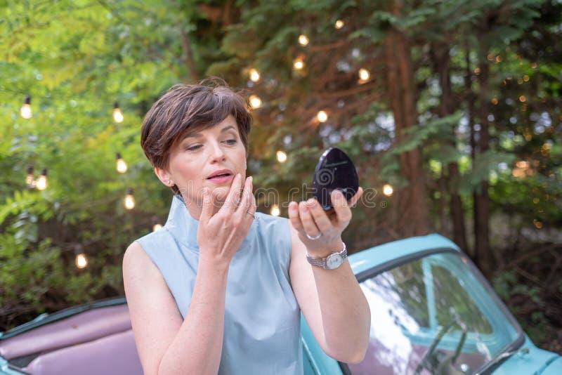 Verticale de femme attirante Femme mignonne d'affaires ajustant ou corrigeant son maquillage sur l'air ouvert photographie stock