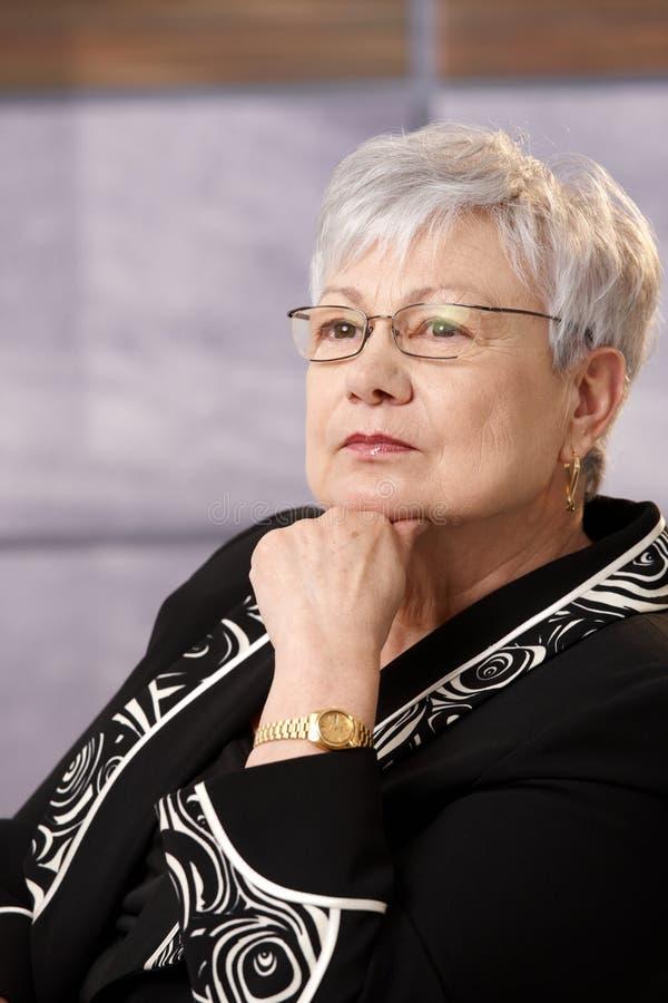 Verticale de femme d'affaires aînée dans la pensée photographie stock