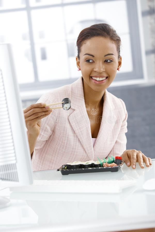 Verticale de femme d'affaires mangeant des sushi photographie stock libre de droits